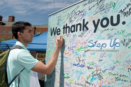 Left to right: In the days leading up to Alumni Weekend, thousands of Homewood undergraduates signed a giant thank-you card that was presented to alumni at a luncheon honoring scholarship supporters